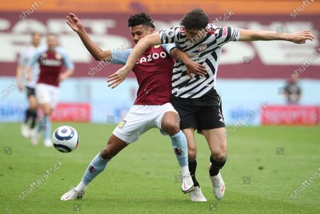 Aston Villa's Ollie Watkins, left, duels for the ball with Manchester United's Harry Maguire during the English Premier League soccer match between Aston Villa and Manchester United at Villa Park in Birmingham, England