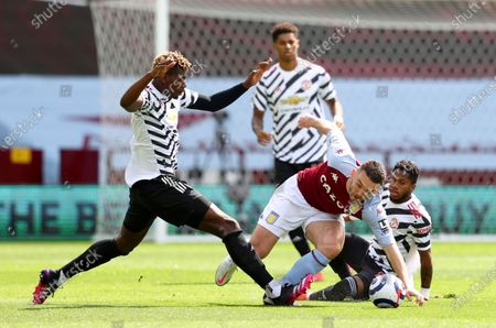 Aston Villa's John McGinn, right, duels for the ball with Manchester United's Paul Pogba, left, during the English Premier League soccer match between Aston Villa and Manchester United at Villa Park in Birmingham, England