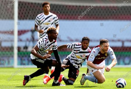 Aston Villa's John McGinn, right, duels for the ball with Manchester United's Fred, second right, and Manchester United's Paul Pogba during the English Premier League soccer match between Aston Villa and Manchester United at Villa Park in Birmingham, England