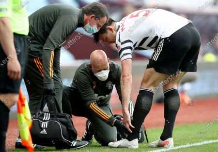 Harry Maguire (R) of Manchester United receives medical help after injuring during the English Premier League soccer match between Aston Villa and Manchester United in Birmingham, Britain, 09 May 2021.