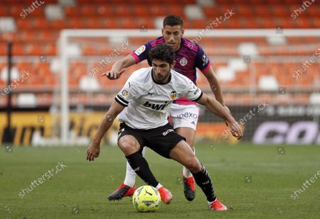 Valencia's winger Goncalo Guedes (L) duels for the ball against Valladolid's midfielder Ruben Alcaraz (R) during the Spanish LaLiga soccer match between Valencia CF and Real Valladolid at San Mames stadium in Valencia, eastern Spain, 09 May 2021.