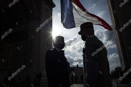 Stock Photo of French President Emmanuel Macron speaks with General Francois Lecointre during a ceremony marking the 76th anniversary of Victory in Europe (Ve-day), marking the end of World War II in Europe, in Paris on May 8, 2021. The leader of the Free French Forces, Charles De Gaulle, announced the official end of World War II to the French people on May 8, 1945, marking the end of a six-year war and the Nazi oppression in France, which resulted in millions of deaths.