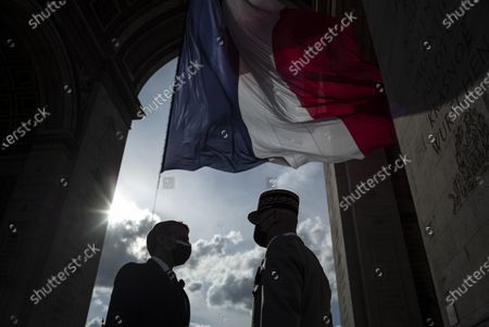 French President Emmanuel Macron speaks with General Francois Lecointre during a ceremony marking the 76th anniversary of Victory in Europe (Ve-day), marking the end of World War II in Europe, in Paris on May 8, 2021. The leader of the Free French Forces, Charles De Gaulle, announced the official end of World War II to the French people on May 8, 1945, marking the end of a six-year war and the Nazi oppression in France, which resulted in millions of deaths.