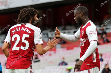 Arsenal's Nicolas Pepe, right, celebrates with Arsenal's Mohamed Elneny after scoring his side's second goal during the English Premier League soccer match between Arsenal and West Bromwich Albion at the Emirates Stadium in London, England
