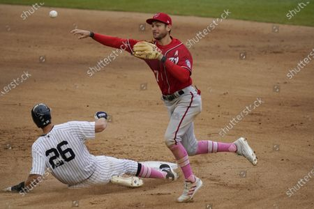Washington Nationals shortstop Trea Turner, right, turns a double play over New York Yankees' DJ LeMahieu during the seventh inning of a baseball game on a ball hit by Giancarlo Stanton at Yankee Stadium, in New York