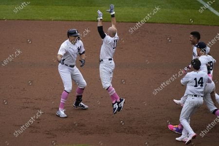 New York Yankees' Giancarlo Stanton, left, celebrates his walkoff single with teammates during the ninth inning of a baseball game against the Washington Nationals at Yankee Stadium, in New York