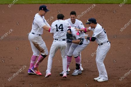 Stock Photo of Teammates mob New York Yankees' Giancarlo Stanton, center, after he hit a walkoff single during the ninth inning of a baseball game against the Washington Nationals at Yankee Stadium, in New York