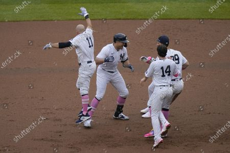 Teammates mob New York Yankees' Giancarlo Stanton, second from left, after he hit a walkoff single during the ninth inning of a baseball game against the Washington Nationals at Yankee Stadium, in New York