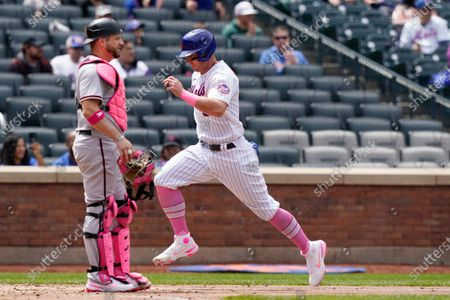 New York Mets James McCann, right, scores on Francisco Lindor's sacrifice fly during a baseball game against the Arizona Diamondbacks, in New York. Diamondbacks catcher Stephen Vogt, left, looks on