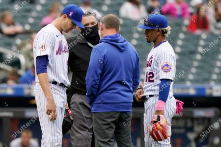 New York Mets starting pitcher Jacob deGrom, left, reacts before leaving the mound without throwing a pitch during the sixth inning of a baseball game against the Arizona Diamondbacks, in New York. Home plate umpire Manny Gonzalez, second from left, the Mets trainer, second from right, and Mets shortstop Francisco Lindor (12) look on