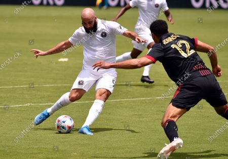 Inter Miami forward Gonzalo Higuain (9) shoots on goal as Atlanta United defender Miles Robinson (12) defends on the play during the first half of an MLS soccer match, in Fort Lauderdale, Fla