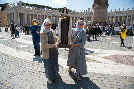 Two nuns hold the statue of saint Teresa di Lisieux as they attend Pope Francis ' Angelus noon prayer in St. Peter's Square at the Vatican