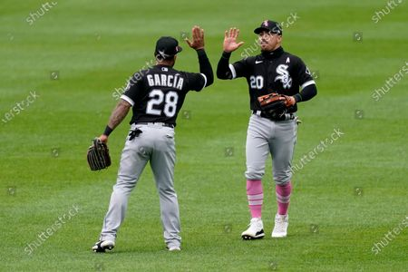 Chicago White Sox left fielder Leury Garcia (28) and Danny Mendick (20) celebrate after their baseball game against the Kansas City Royals, in Kansas City, Mo. The White Sox won 9-3