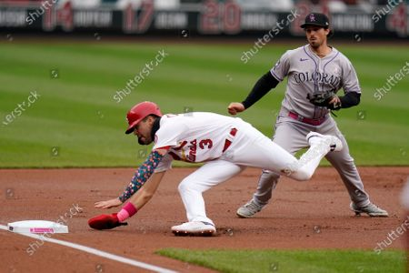 St. Louis Cardinals' Dylan Carlson (3) falls trying to make it to third after being tagged out by Colorado Rockies third baseman Josh Fuentes, right, during the first inning of a baseball game, in St. Louis