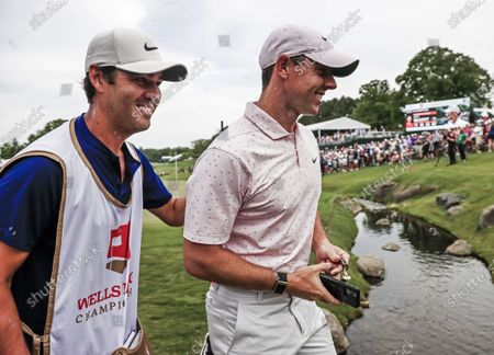 Rory McIlroy of Northern Ireland (R) and caddie Harry Diamond (L) walk off the eighteenth green after the fourth round of the Wells Fargo Championship golf tournament at Quail Hollow Club in Charlotte, North Carolina, USA, 09 May 2021. McIlroy worn the tournament with a score of 10 under par.