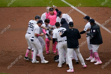 Stock Image of Teammates mob New York Yankees' Giancarlo Stanton, center, after he hit a walk-off single during the ninth inning of a baseball game against the Washington Nationals at Yankee Stadium, in New York. The Yankees defeated the Nationals 3-2
