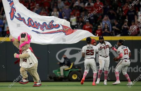 Atlanta Braves outfielders Cristian Pache (25), Marcell Ozuna, and Ronald Acuna Jr. (13) right, celebrate the 6-1 victory over the Philadelphia Phillies at the end of a baseball game, in Atlanta