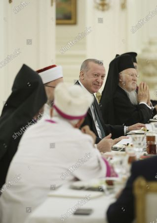 Turkey's President Recep Tayyip Erdogan, center, holds a traditional Iftar dinner breaking the fast during the Muslim holy month of Ramadan, with religions leaders in Ankara, Turkey, . Iftar is the meal eaten by Muslims after sunset during Ramadan, the Islamic period of fasting when they cannot eat or drink during sunlight hours
