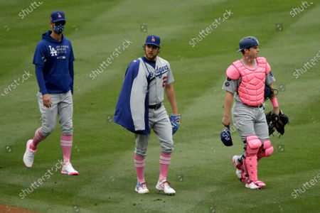 Los Angeles Dodgers starting pitcher Trevor Bauer, center, walks to the dugout with catcher Will Smith, right, and pitching coach Mark Prior after warming up for a baseball game against the Los Angeles Angels in Anaheim, Calif