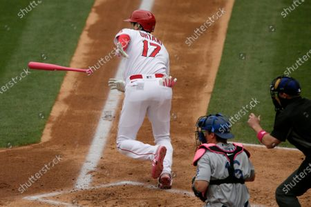 Los Angeles Angels designated hitter Shohei Ohtani, left, runs to first for an infield single, with Los Angeles Dodgers catcher Will Smith, and home plate umpire Tripp Gibson, right, watching, during the first inning of a baseball game in Anaheim, Calif