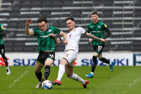 Stock Image of Rochdale's Ollie Rathbone is challenged by Milton Keynes Dons Josh McEachran during the first half of the Sky Bet League One match between MK Dons and Rochdale at Stadium MK, Milton Keynes, UK on 9th May 2021.