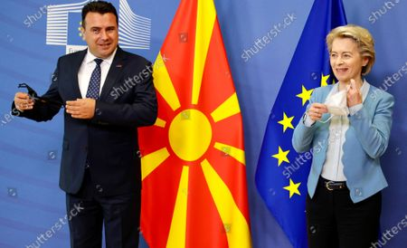 European Commission President Ursula von der Leyen, right, and North Macedonia's Prime Minister Zoran Zaev take off their protective face masks prior to an official greeting at EU headquarters in Brussels