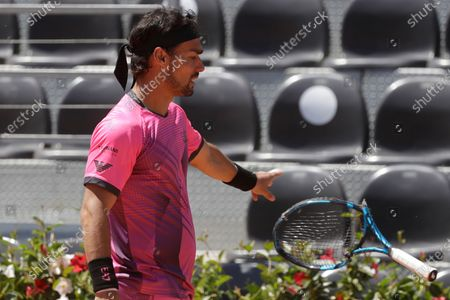 Italy's Fabio Fognini throws away his racket after breaking it during his match against Japan's Kei Nishikori at the Italian Open tennis tournament, in Rome