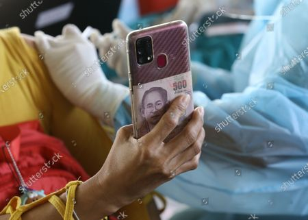 Stock Photo of A Thai banknote with a picture of late Thai King Bhumibol Adulyadej is seen on the back of the mobile phone of a resident as she takes a picture while getting a shot of CoronaVac vaccine during an emergency vaccination drive against the COVID-19 coronavirus pandemic, in a bid to contain the rapid spreading of the pandemic in Klong Toey slum community, at old warehouse in Bangkok, Thailand, 10 May 2021. The Thai government is conducting emergency vaccinations as well as mass testing in several crowded and low-income communities, following a sharp rise in COVID-19 infections in Bangkok.