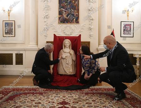Stock Photo of British Museum staff Peter John Higgs (L), Head of Greece and Rome Department, and Hannah Boulton (C), Head of Press and Marketing, and Lybian Embassy Charge d'affaires Mohamed Elkoni (R) pose for photographers next to the Persephone statue is pictured at the Libyan embassy in London, Britain, 10 May 2021. The British Museum and HM Revenue and Customs (HMRC) have collaborated with the Embassy of Libya to assist in the return of a rare 2nd century BC funerary statue from Cyrene. In December 2011, the statue was illegally excavated from an underground site in the historic and UNESCO protected site of Cyrene, Shahat, Lybia. The statue was seized by Border Force officials at Heathrow airport several years ago after having been illicitly imported into the United Kingdom to be offered for sale. In 2013, specialists at the British Museum were asked to assist in the identification of the statue.
