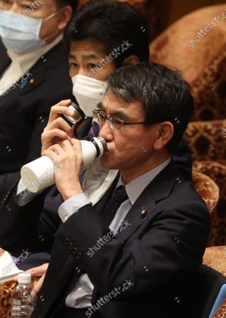 Stock Photo of Japanese Administrative Reform Minister Taro Kono drinks water as he listens to a question at Lower House's budget committee session at the National Diet in Tokyo on Monday, May 10, 2021.