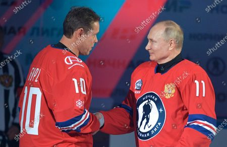 Russian President Vladimir Putin (R) welcomes NHL star and President of the International League of World Hockey Legends, Pavel Bure during a gala match with the participation of Russian hockey legends as part of the final stage of the X All-Russian Night Hockey League festival in the 'Bolshoi' Ice Palac in Sochi, Russia, 10 May 2021.