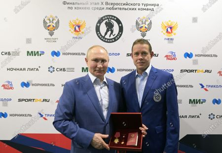 Russian President Vladimir Putin (L) awards Russia's Order of Merit for the Fatherland (4th class) to NHL star and President of the International League of World Hockey Legends, Pavel Bure after a gala match with the participation of Russian hockey legends as part of the final stage of the X All-Russian Night Hockey League festival in the 'Bolshoi' Ice Palac in Sochi, Russia, 10 May 2021.