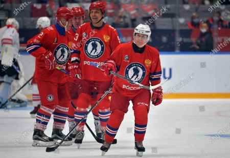 Russian President Vladimir Putin, right, attends a gala match with the participation of Russian hockey legends as part of the final stage of the X All-Russian Night Hockey League festival in the Bolshoi Ice Palace in the Black Sea resort of Sochi, Russia