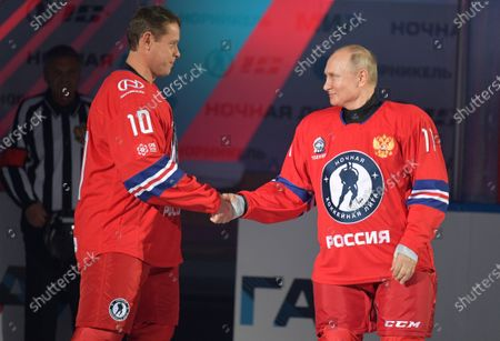 Russian President Vladimir Putin, right, and Russian former ice hockey star Pavel Bure shake hands as they attends a gala match with the participation of Russian hockey legends as part of the final stage of the X All-Russian Night Hockey League festival in the Bolshoi Ice Palace in the Black Sea resort of Sochi, Russia