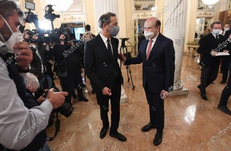 Stock Image of Teatro alla Scala Superintendent, French Dominique Meyer (L),listen to a guest, both wearing a face masks,at the foyer of the Teatro alla Scala to attend the concert directed by the musical director Riccardo Chailly that commemorates the 75th anniversary of the reopening of the Piermarini Hall after the years of the dictatorship, the II World War and the bombing with the historic concert directed by Arturo Toscanini on 11 May 1946, in Milan, Italy, 10 May 2021. Today's concert is the first event with the presence of audience since 19 October 2020. Only 500 tickets of the approximately 2000 seats were made available as required by current anti-covid legislation.