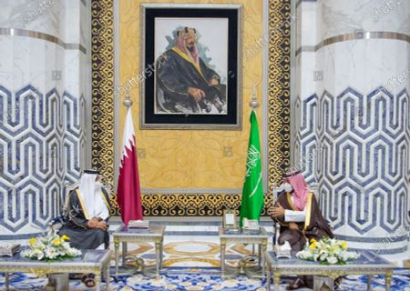 In this photo released by Saudi Royal Palace, Saudi Crown Prince Mohammed bin Salman, right, meets with Qatar's Emir Sheikh Tamim bin Hamad Al Thani in the Red Sea city of Jiddah, Saudi Arabia, . Qatar's ruling emir is visiting Saudi Arabia for the first time since signing a declaration with other Arab Gulf states to ease a years-long rift and end an embargo that had frayed ties among important U.S. allies and security partners. At top a framed photo shows Saudi Arabia's founder, the late King Abdul Aziz Al Saud