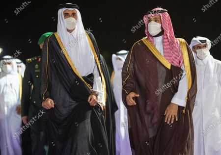 Stock Image of In this photo released by Saudi Royal Palace, Saudi Crown Prince Mohammed bin Salman, right, accompanies Qatar's Emir Sheikh Tamim bin Hamad Al Thani upon his arrival at in the Red Sea city of Jiddah, Saudi Arabia, . Qatar's ruling emir is visiting Saudi Arabia for the first time since signing a declaration with other Arab Gulf states to ease a years-long rift and end an embargo that had frayed ties among important U.S. allies and security partners