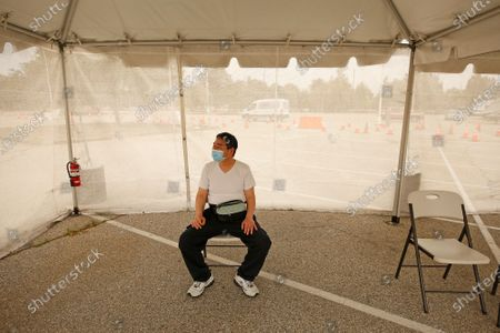 Mitsu Ishii, 52, from Calabasas waits alone in the observation area after receiving the Johnson & Johnson vaccination at Pierce College in Woodland Hills as the Los Angeles Fire Department, CORE and Carbon Health, are making Covid-19 vaccination available for walk-ins starting today, Monday May 10, 2021. Los Angeles will offer appointment-free COVID-19 vaccinations at all of its city-run sites and open two additional night clinics in a new effort to expand vaccine access, Mayor Eric Garcetti said. All three vaccination options - Pfizer, Moderna, Johnson & Johnson are currently available at Pierce College. Pierce College on Monday, May 10, 2021 in Woodland Hills, CA. ({a} / Los Angeles Times).