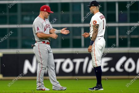 Houston Astros' Carlos Correa (1) talks with Los Angeles Angels' Mike Trout before a baseball game, in Houston