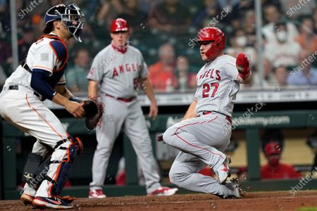 Los Angeles Angels' Mike Trout (27) scores as Houston Astros catcher Jason Castro waits for the throw during the fourth inning of a baseball game, in Houston