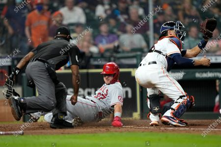 Los Angeles Angels' Mike Trout (27) scores as Houston Astros catcher Jason Castro reaches for the throw during the fourth inning of a baseball game, in Houston