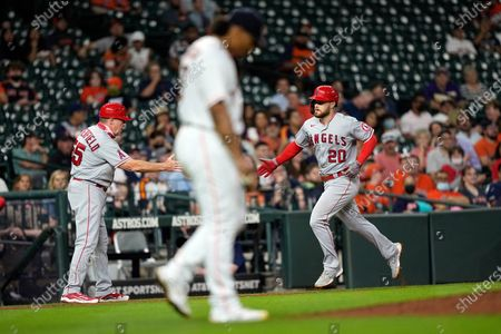 Los Angeles Angels' Jared Walsh (20) celebrates with third base coach Brian Butterfield (55) after hitting a home run off Houston Astros starting pitcher Luis Garcia, center, during the sixth inning of a baseball game, in Houston
