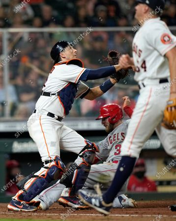 Los Angeles Angels' Taylor Ward (3) scores as Houston Astros catcher Jason Castro, left, reaches for the throw from relief pitcher Brandon Bielak (64) during the sixth inning of a baseball game, in Houston
