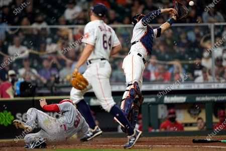 Los Angeles Angels' Taylor Ward (3) scores as Houston Astros catcher Jason Castro, right, reaches for the throw from relief pitcher Brandon Bielak (64) during the sixth inning of a baseball game, in Houston