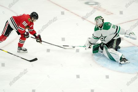 Dallas Stars goaltender Jake Oettinger, right, keeps Chicago Blackhawks' Patrick Kane from getting a shot off during the second period of an NHL hockey game, in Chicago