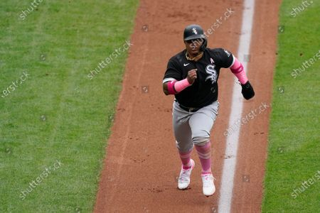 Chicago White Sox's Yermin Mercedes runs home past Kansas City Royals catcher Salvador Perez to score on a sacrifice fly hit by Leury Garcia during the second inning of a baseball game, in Kansas City, Mo