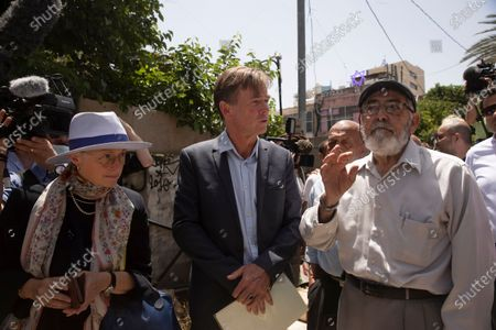 Sven Kuhn von Burgsdorff, center, the European Union representative for the Palestinian Territories, listens to Nabil al-Kurd, a resident of the Sheikh Jarrah neighborhood of east Jerusalem, who is from one of several Palestinian families under threat of forced eviction, . Behind them is a Palestinian home now occupied by Jewish settlers