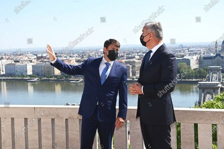 Montenegrin President Milo Djukanovic (R) listens to his Hungarian counterpart Janos Ader (L) on the terrace of the presidential Alexander Palace, With River Danube in the background, in Budapest, Hungary, 11 May 2021.