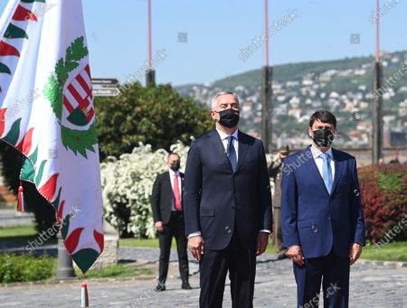 Montenegrin President Milo Djukanovic (L) and his Hungarian counterpart Janos Ader (R) listen to the national anthems during the welcoming ceremony at the presidential Alexander Palace in Budapest, Hungary, 11 May 2021.