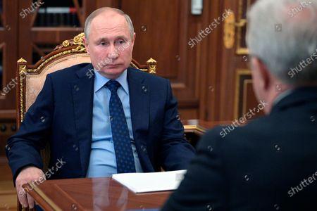 Russian President Vladimir Putin, left, listens to governor of Krasnoyarsk Region Alexander Uss during their meeting in Moscow, Russia